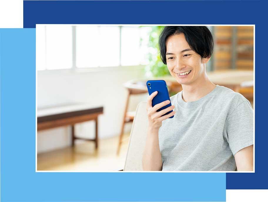 スマホで笑顔で応募する男性のイメージ画像